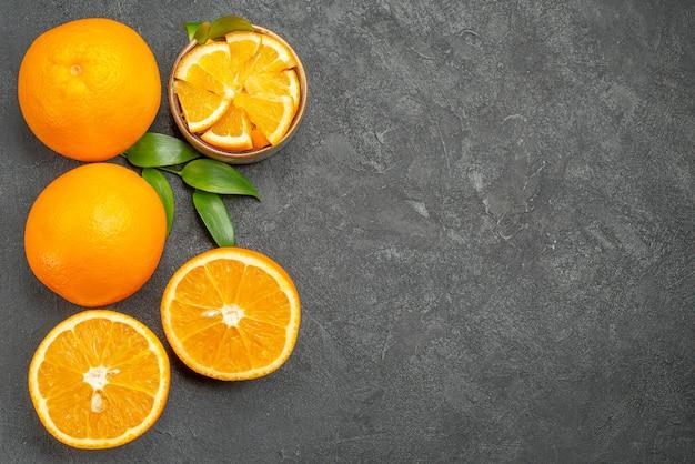 Visualização horizontal de um conjunto de laranjas amarelas inteiras e picadas na mesa escura