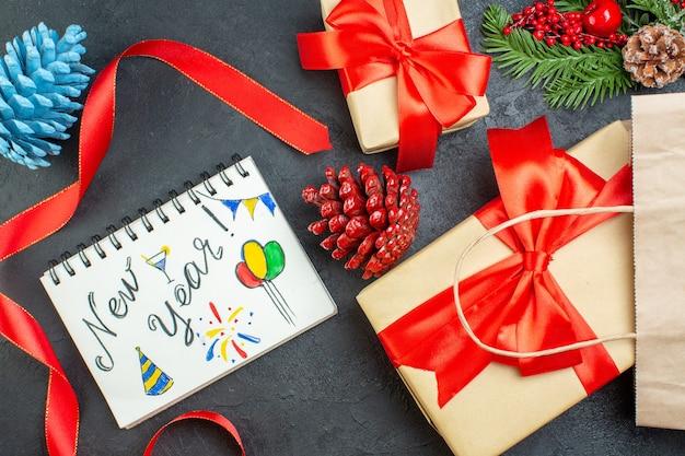 Visualização horizontal de um rolo de cones de coníferas de fita vermelha e um caderno de ramos de abeto com desenhos de ano novo na mesa escura