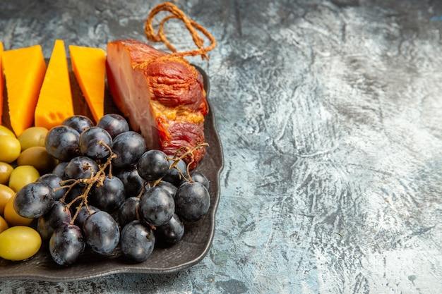 Visualização horizontal do delicioso melhor lanche para vinho na bandeja marrom no fundo de gelo