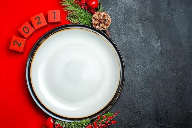 Visualização horizontal do plano de fundo do ano novo com acessórios de decoração de prato de jantar ramos de abeto e números em um guardanapo vermelho sobre uma mesa preta