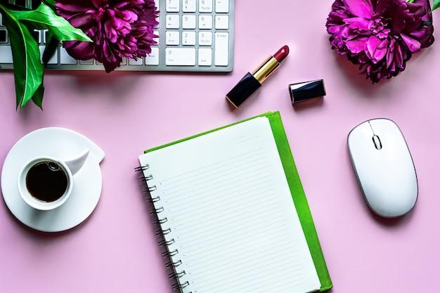 Visualização plana da área de trabalho. caderno com lista de afazeres, acessórios de computador, peônias bordô brilhantes, café preto e batom feminino, sobre um fundo rosa claro.
