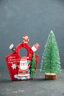Visualização vertical do clima de natal com acessórios de decoração na caixa de presente de ano novo e árvore de natal na superfície escura