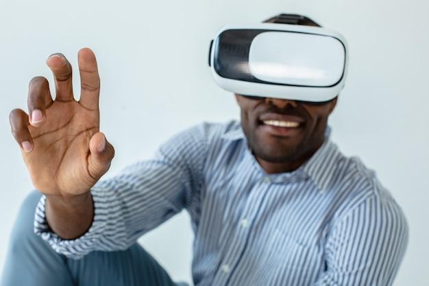 Visualize seus sonhos. homem afro-americano bonito e positivo usando óculos de realidade virtual enquanto expressa alegria