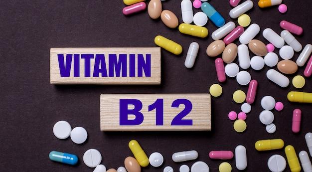 Vitamin b12 é escrito em blocos de madeira perto de pílulas multicoloridas. conceito médico
