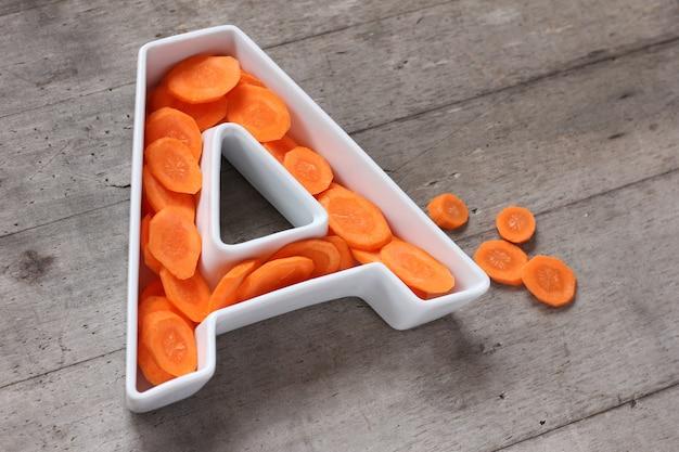 Vitamina a no conceito de comida. placa em forma de letra a com cenouras frescas em fatias.