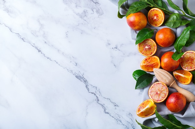 Vitamina, alimentação limpa, conceito vegan de comida saudável. laranjas doces sicilianas inteiras e fatiadas sobre uma mesa de mármore branco. vista superior do plano de fundo do espaço da cópia