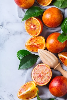 Vitamina, alimentação limpa, conceito vegan de comida saudável. laranjas doces sicilianas inteiras e fatiadas sobre uma mesa de mármore branco. vista superior do plano de fundo