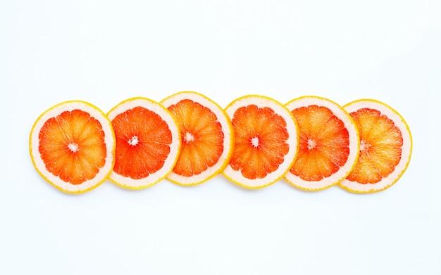 Vitamina alta c. fatias de toranja suculenta em fundo branco. vista do topo
