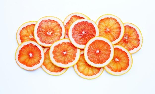 Vitamina alta c. fatias de toranja suculenta em fundo branco.