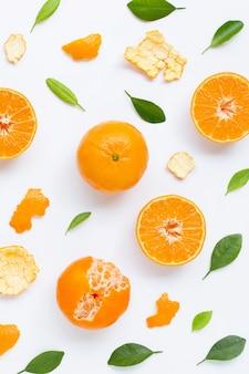 Vitamina alta c. tanjerina fresca com as folhas no fundo branco.