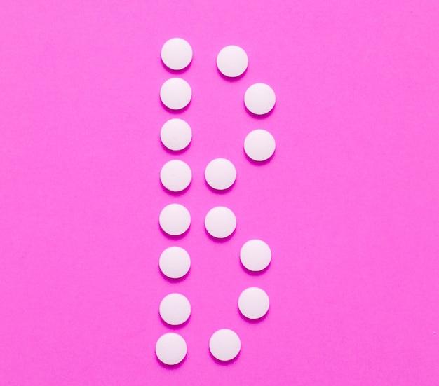 Vitamina b. letra b de comprimidos brancos em fundo rosa. conceito médico minimalista. vista do topo.