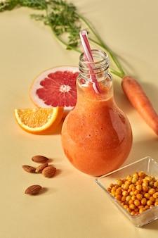 Vitamina bebida com cenoura, espinheiro, toranja e laranja em um copo com um canudo em um fundo de papel laranja. alimentação saudável