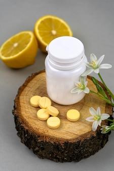 Vitamina c em um frasco branco em uma placa de madeira com limões e flores comprimidos amarelos e limão