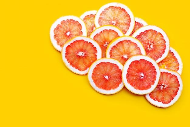 Vitamina c. fatias de toranja suculenta na superfície amarela
