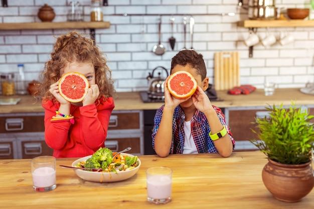Vitamina c. garota loira incrível olhando diretamente para a câmera e sentada perto de sua amiga internacional