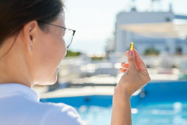 Vitamina d, e, a cápsula de óleo de peixe ômega de óleo de fígado de bacalhau na mão feminina