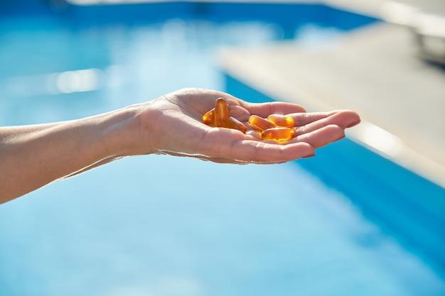 Vitamina d, e, a cápsulas de óleo de peixe óleo de fígado de bacalhau ômega 3 em mãos femininas