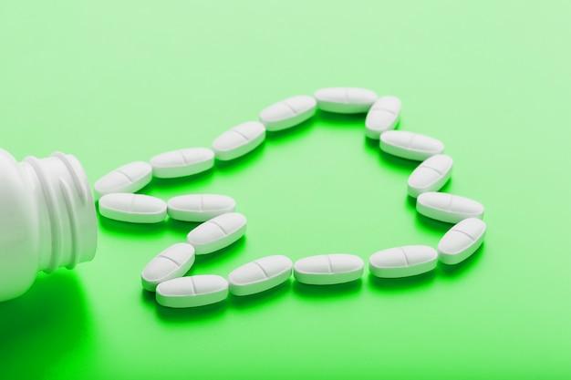 Vitamina de cálcio na forma de um dente derramado de um frasco branco em um verde.