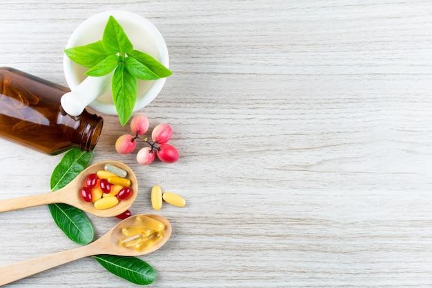 Vitamina orgânica natural e suplementos, folhas de argamassa no conceito de fundo de madeira, medicamentos e drogas