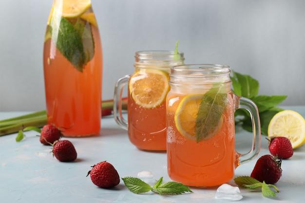 Vitamina saudável ruibarbo e morango bebida de verão com hortelã, limão e gelo em uma mesa de concreto azul claro, formato horizontal, close-up