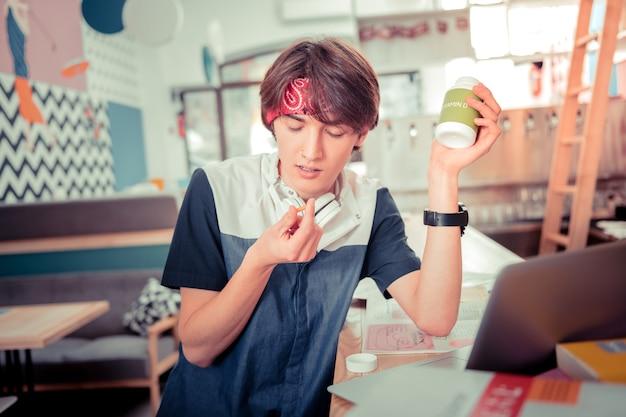 Vitaminas adicionais. o adolescente tomando pílulas de vitamina d enquanto se prepara para o exame