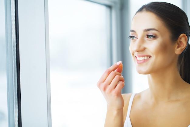 Vitaminas. alimentação saudável. menina feliz com cápsula de óleo de peixe omega-3. conceito de dieta saudável.