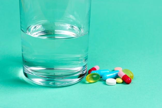 Vitaminas, analgésicos, antibióticos e um copo de água, medicamentos
