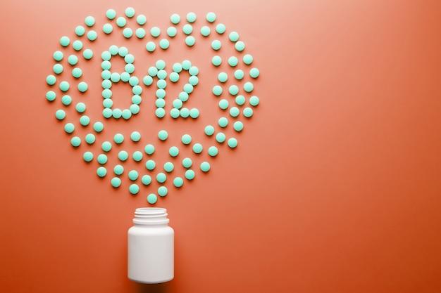 Vitaminas b 12 em forma de coração em um substrato vermelho, derramado de um frasco branco.