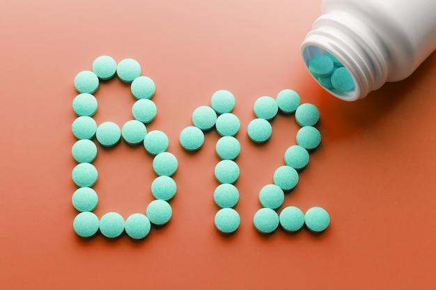 Vitaminas b 12 em um substrato vermelho, derramado de um frasco branco.