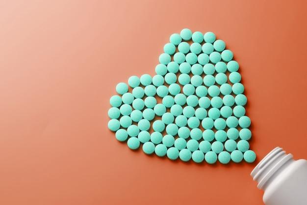 Vitaminas b 12 em um substrato vermelho em forma de coração, derramado de um frasco branco.