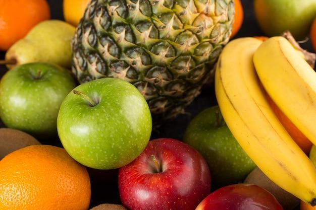 Vitaminas coloridas de frutas frescas ricas maduras maduras maçãs verdes bananas e outros na mesa cinza