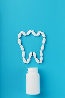 Vitaminas com cálcio na forma de um dente derramado de um frasco branco sobre fundo azul