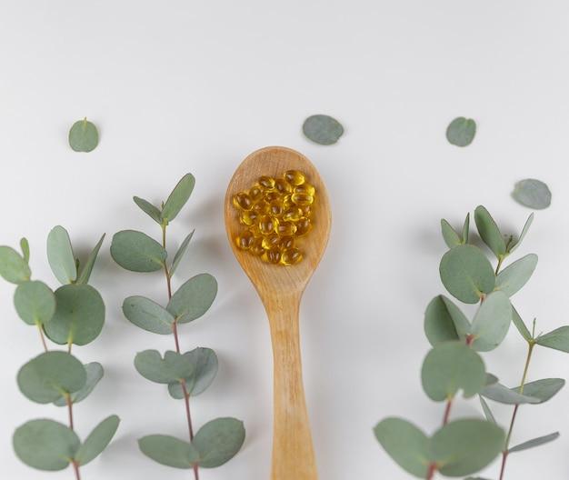 Vitaminas d em uma colher com galhos de eucalipto