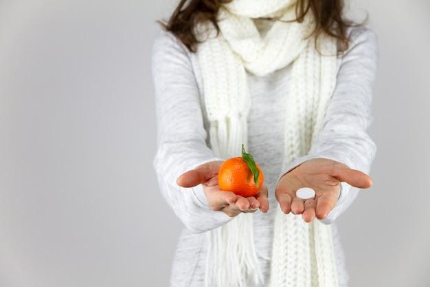 Vitaminas de frutas ou drogas? uma jovem doente com um lenço no pescoço mostra uma tangerina na mão direita e uma aspirina na esquerda