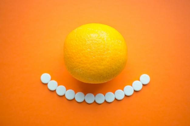 Vitaminas de verão. fruta laranja e comprimidos brancos redondos como sorriso