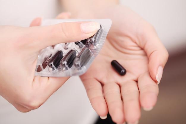 Vitaminas e suplementos. close up das mãos da mulher que guardam a variedade de comprimidos coloridos da vitamina. punhado do close-up da medicamentação, tabuletas da medicina, cápsulas. nutrição dieta saudável. alta resolução