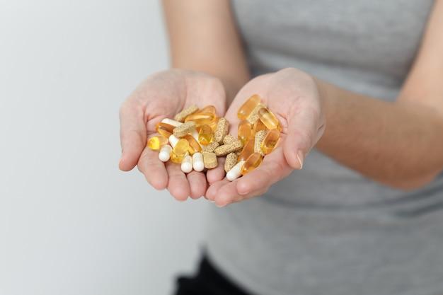 Vitaminas e suplementos. closeup de mãos de mulher segurando uma variedade de pílulas de vitamina coloridas. punhado de close-up de medicamentos, comprimidos de remédios, cápsulas. conceito de nutrição dieta saudável. alta resolução