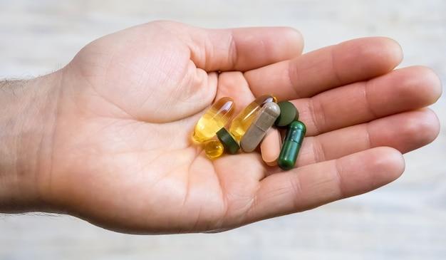 Vitaminas e suplementos dietéticos em uma mão. foco seletivo. pessoas.
