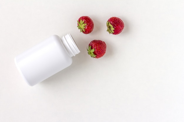 Vitaminas frescas como morangos do frasco de comprimidos de medicamento branco.