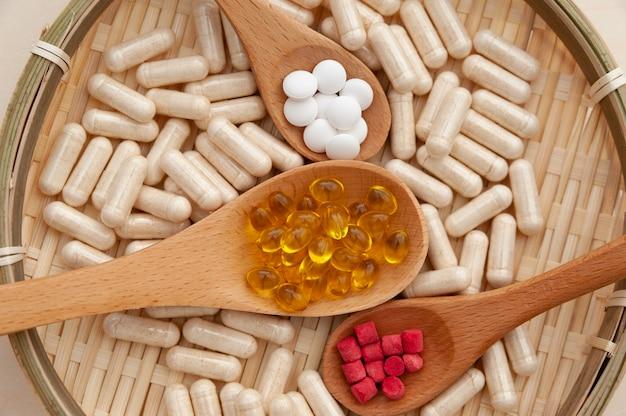 Vitaminas, minerais e suplementos nutricionais em colheres de madeira dentro de uma placa de bambu trançado