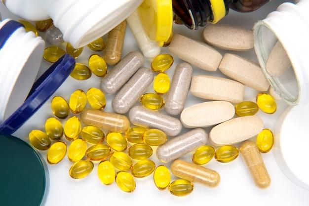 Vitaminas, ômega 3, óleo de fígado de bacalhau, suplemento dietético e comprimidos de um aterro sobre um fundo claro close-up