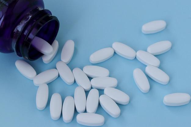 Vitaminas para fortalecer as articulações, glucosamina, sobre um fundo azul claro