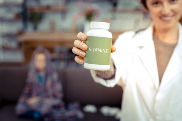 Vitaminas úteis. foco seletivo de um frasco com vitamina d nas mãos de uma médica positiva