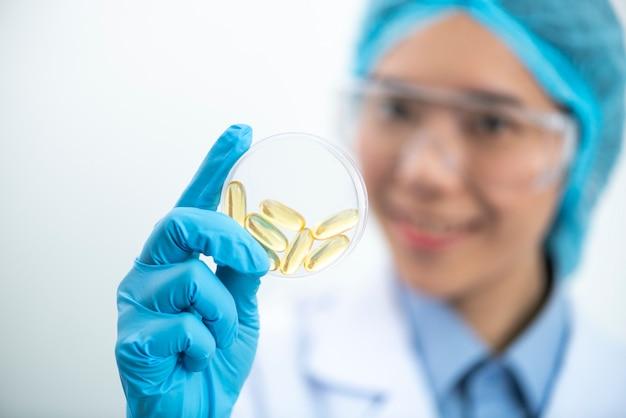 Vitamins.close up of girl holding pílula com óleo de fígado de bacalhau omega