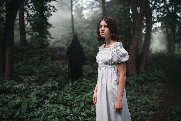 Vítima feminina e morte com capuz preto na floresta