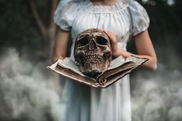 Vítima feminina segurando livro e crânio humano