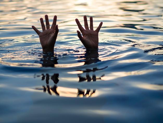 Vítimas de afogamento, mão de homem se afogando precisando de ajuda.