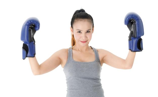 Vitoriosa jovem lutadora asiática com luvas de boxe azuis, levantando as mãos e sorrindo alegremente enquanto celebra o triunfo contra um fundo branco