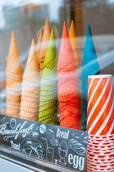 Vitrina de vidro em uma sorveteria cones com muitos cones para cornetas de sorvete. comida refrescante de verão na rua do calor fast food para levar