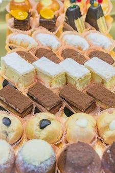 Vitrine de pastelaria com variedade de mini sobremesas e bolos, barra de chocolate